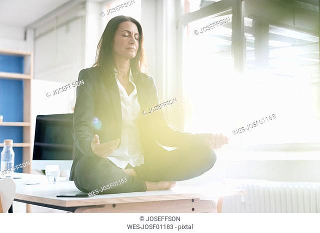 Businesswoman doing yoga exercise on desk in a loft