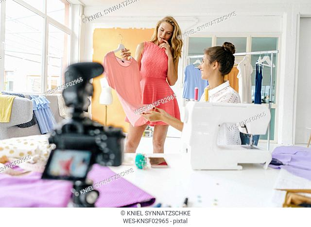 Two young women in fashion studio with camera