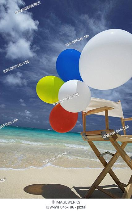 View of air balloons on wooden chair at beach