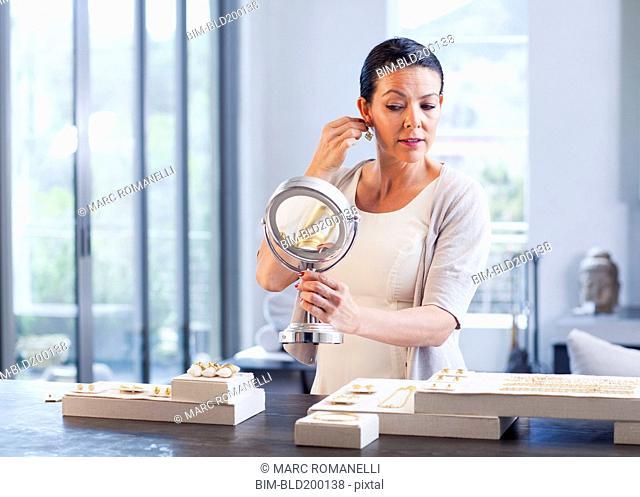 Hispanic woman trying on earrings in jewelry store
