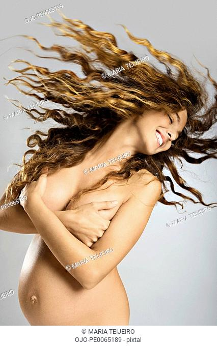 Nude, pregnant woman swing her long hair