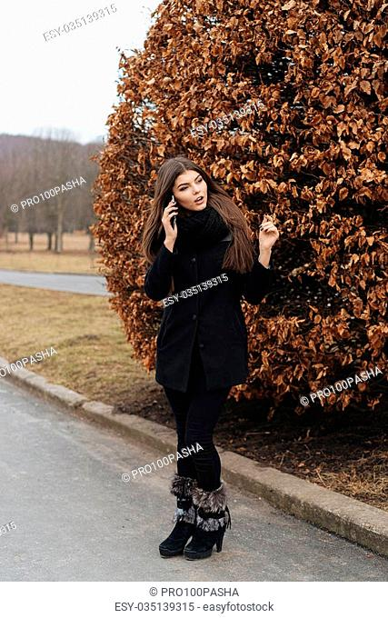 Beautiful girl with phone in autumn park near tree