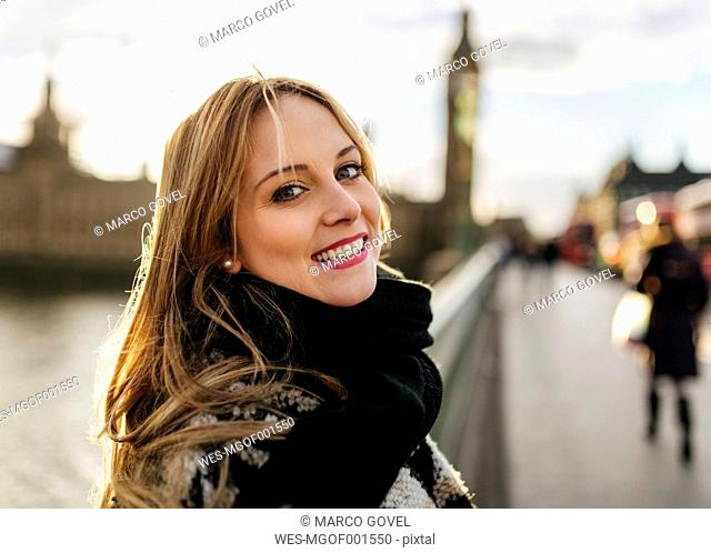 UK, London, portrait of smiling young woman on Westminster Bridge