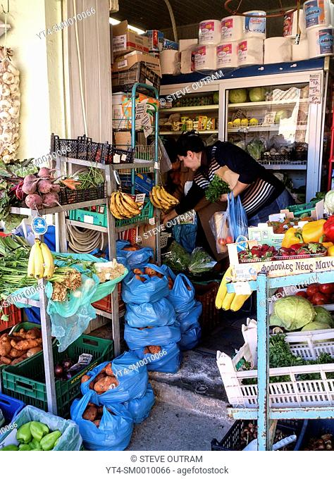 Woman buying produce from a Greengrocers, Crete, Greece