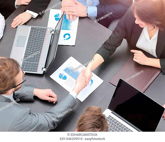 concept of partnership. handshake financial partners at your Desk