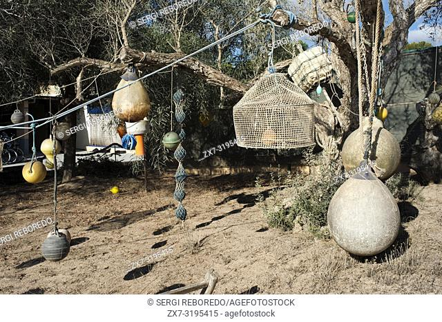 Fishing instruments with nets longlines buoy tackle in foreground hangin in a tree at Formentera, Balearic Island, Spain. Mediterranean sea