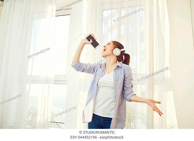A girl in headphones sings a song against the window in the morning