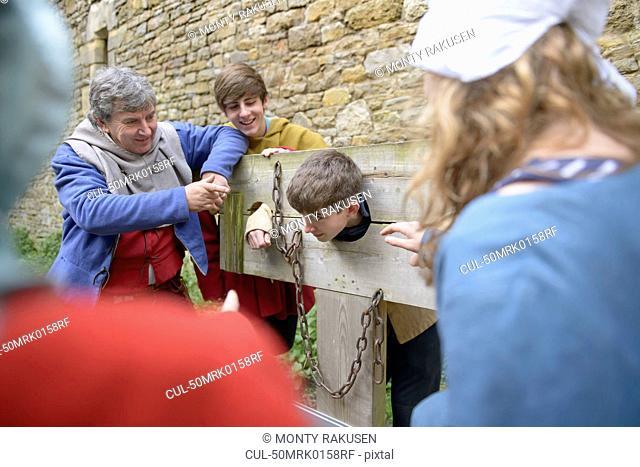 Students examining medieval stocks