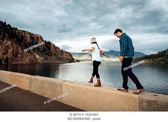 Couple walking along wall beside Dillon Reservoir, Silverthorne, Colorado, USA