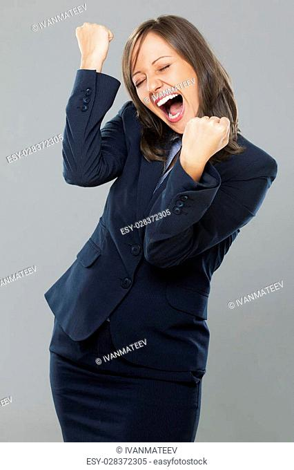 Businesswoman punching the air full of joy isolated on gray background, expressing success