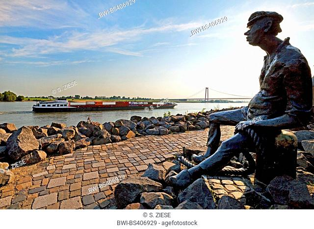 Poortekerl sitting at the promenade and looking over the Rhine with cargo ship and Rhine Bridge , Germany, North Rhine-Westphalia, Lower Rhine, Emmerich