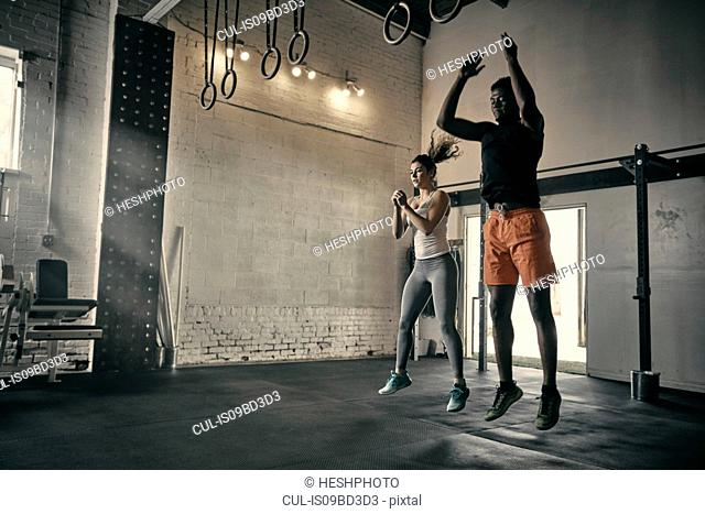 Man and woman in gym jumping in mid air