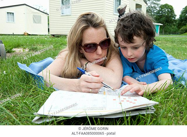 Mother and young son lying on blanket, working puzzles in newspaper together