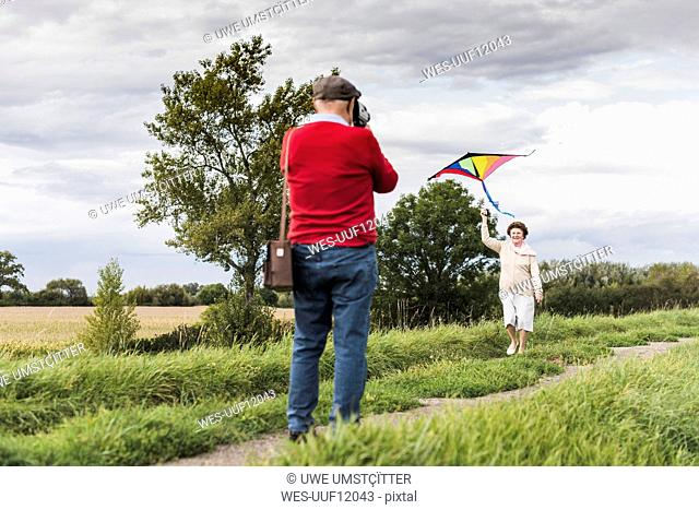 Senior man filming wife flying kite in rural landscape