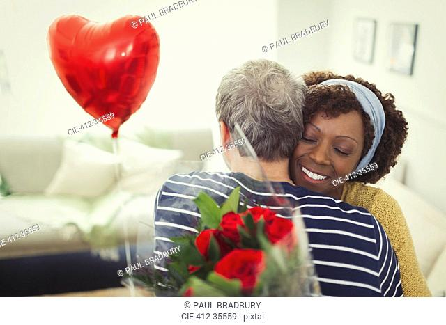 Wife hugging husband giving Valentine's Day balloon and rose bouquet
