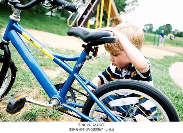 Young Boy Working on Bicycle