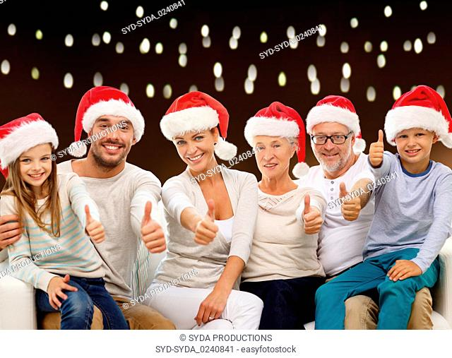 family in christmas santa hats showing thumbs
