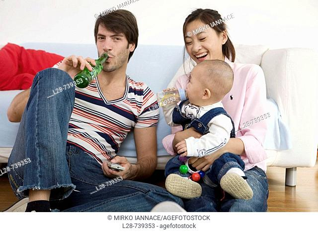 Parents with baby boy (6-11 months) sitting on sofa, smiling