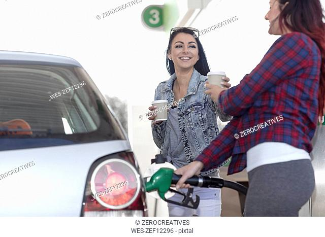 Two women with takeaway coffee fueling car at gas station