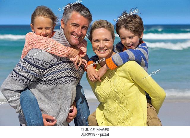 Portrait of happy parents piggybacking children on sunny beach