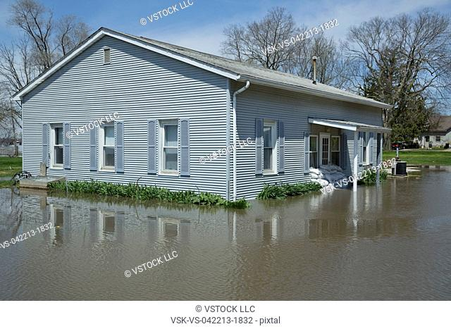 Facade of flooded house with wall made of bags with sand