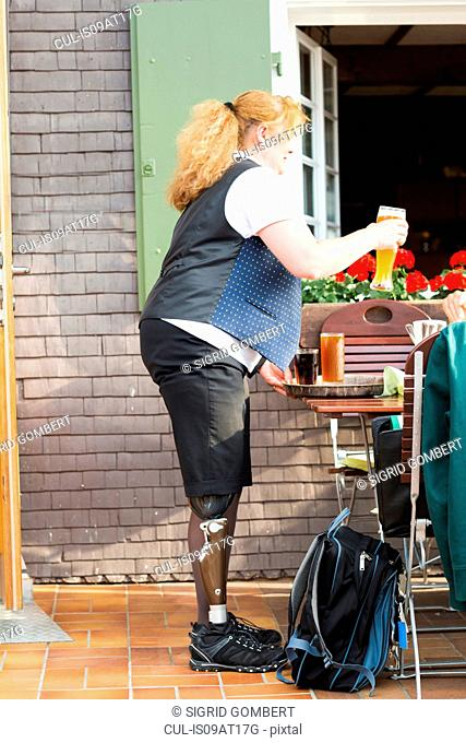 Mid adult woman with prosthetic leg, bringing customer drinks at restaurant