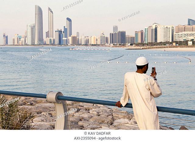 Local UAE man looking at Abu Dhabi cityscape; Abu Dhabi, United Arab Emirates