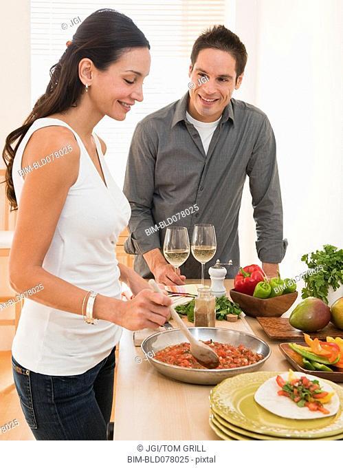 Hispanic couple cooking dinner