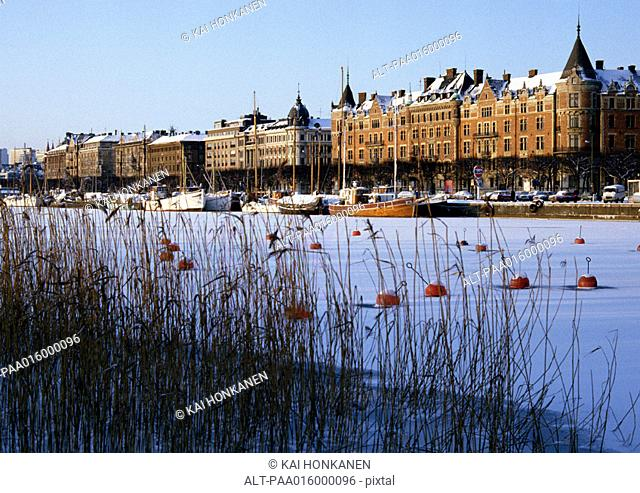 Sweden, Stockholm, snow covered harbor and buildings along quay