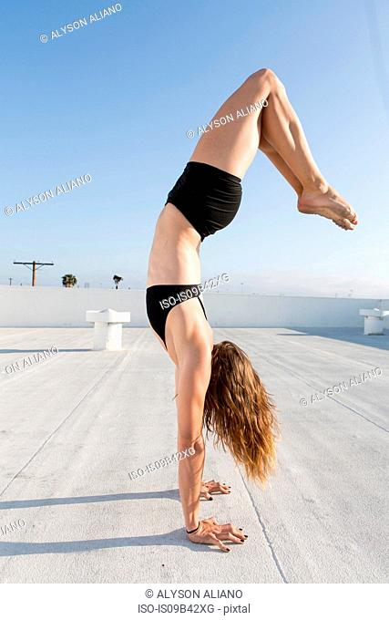 Young woman practicing handstand yoga pose on rooftop
