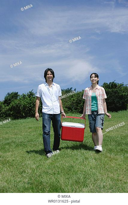 Young couple carrying cooler
