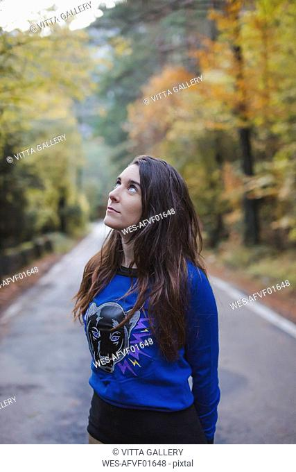 Young woman standing on country road looking up