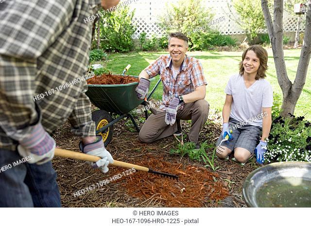 Multi-generation family spreading bark dust in backyard