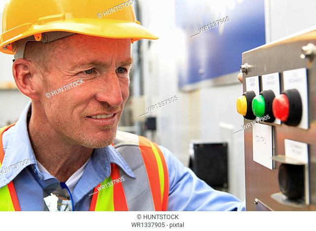 Engineer at electric power plant examining carbon dioxide controls and indicators
