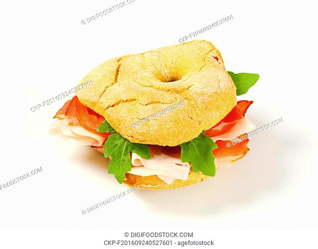 Ring-shaped bread roll with slices of prosciutto