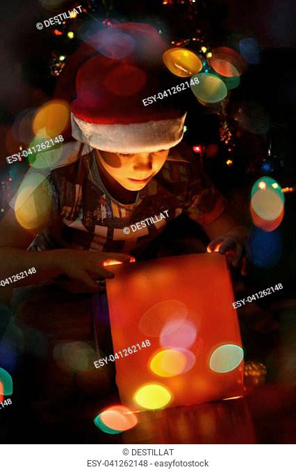 Happy little boy opens his magic glowing christmas gift near decorated christmas tree
