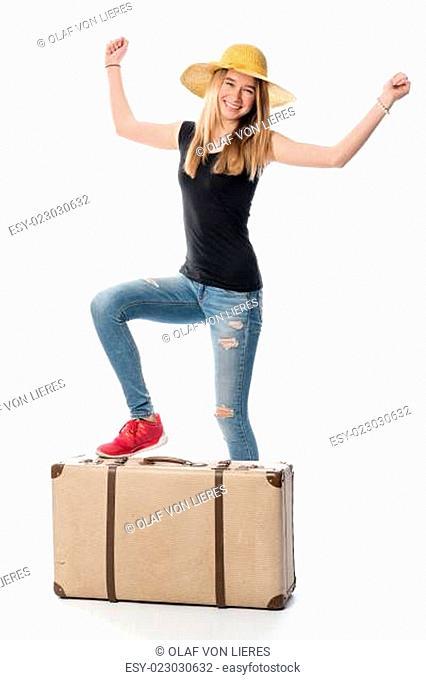 Mädchen steht mit einem Bein auf einem Reisekoffer und jubelt