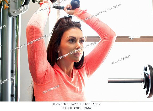 Woman in gym using exercise machine