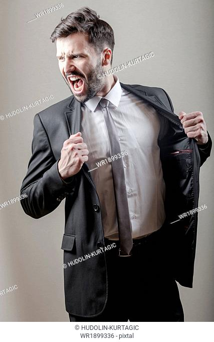 Businessman screaming while clenching fists