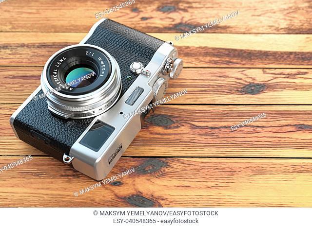 Modern mirrorless camera stilized to retro vintage film camera on wood table background. 3d illustration