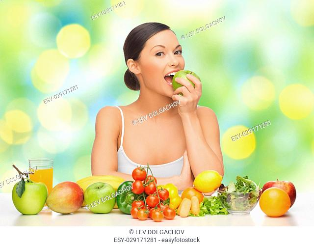 diet, food and people concept - happy woman eating green apple with lot of fruits and vegetables on table over summer lights background