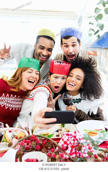 Silly friends in paper crowns taking selfie at Christmas dinner