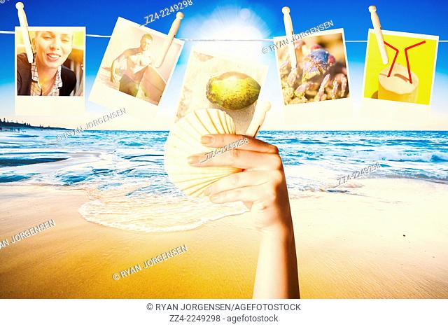Tropical beach landscape photo on the hand of a woman holding sea shell and peg when collecting and hanging photographic memories from a summer vacation to...