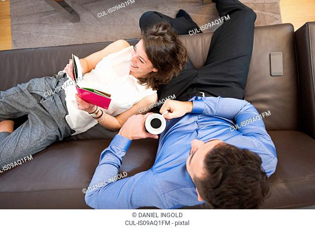 Overhead view of couple reading book and drinking coffee on sofa