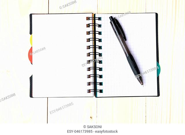 notepad with pen isolated on wood background