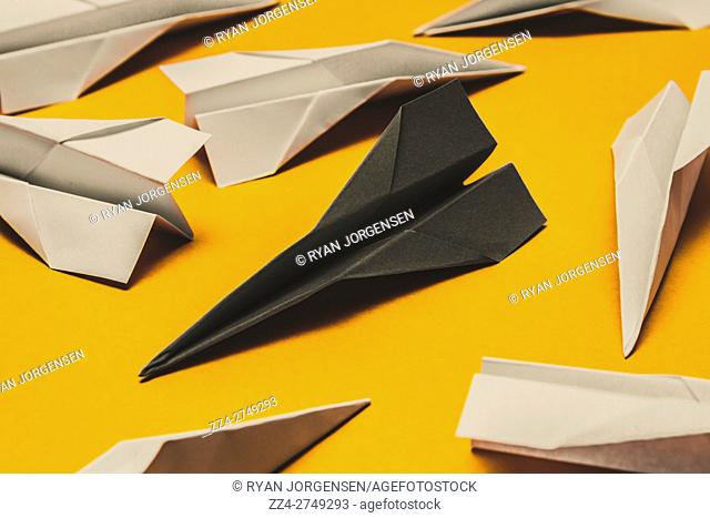 Origami paper planes mismatched in shades of black and white on yellow background. Metaphor of contrast