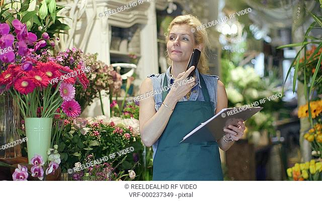 A Florist speaks on the phone, inspecting the supplies in her shop and noting it on her clipboard