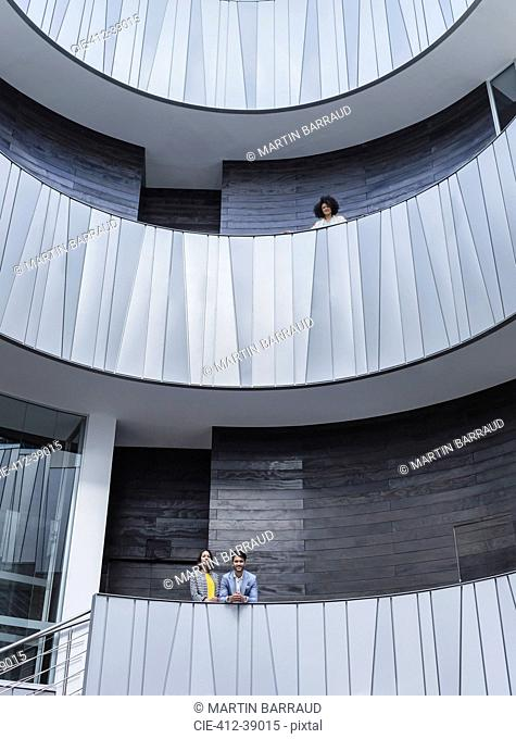 Portrait business people standing on architectural, modern office atrium balconies