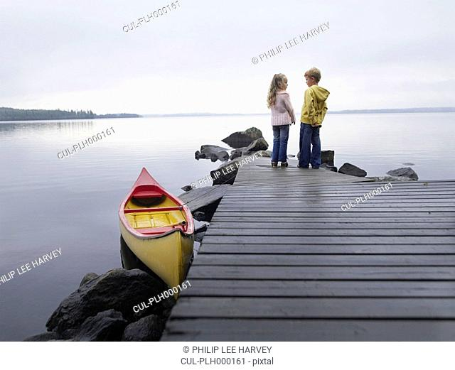Young girl and young boy on a dock near a boat
