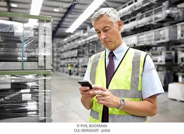 Portrait of manager using mobile phone in engineering warehouse